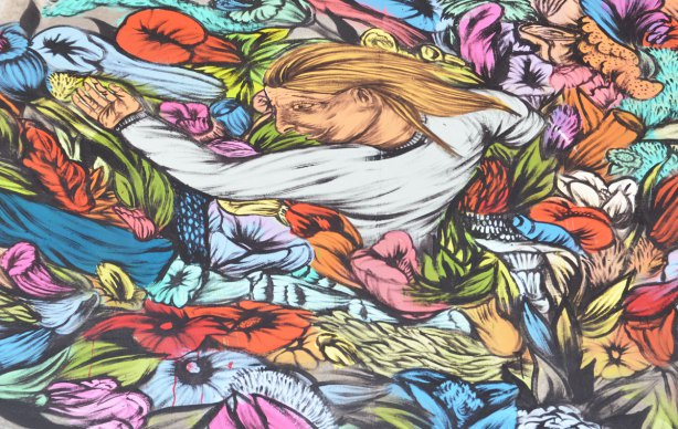 street artist painting of a woman with long yellow hair emerging from a bed of flowers.